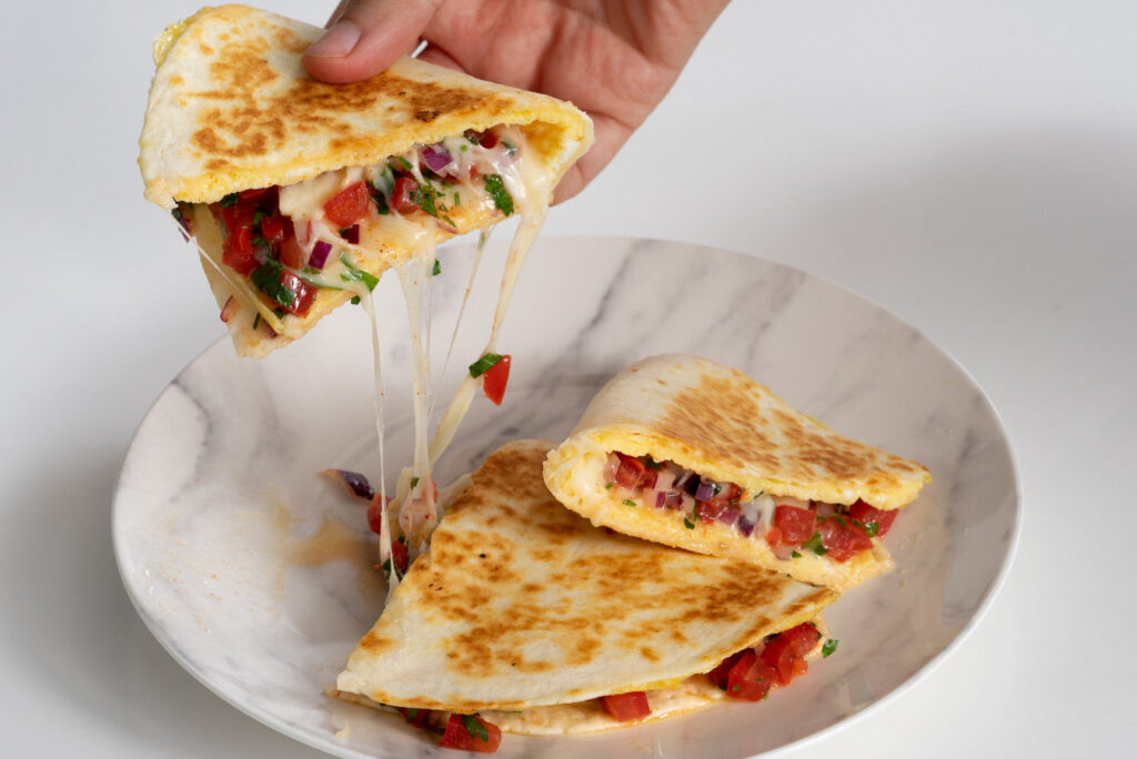 Breakfast sandwich with scrambled eggs, tomatoes and cheese